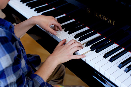 Boy playing piano. Piano lessons in NYC
