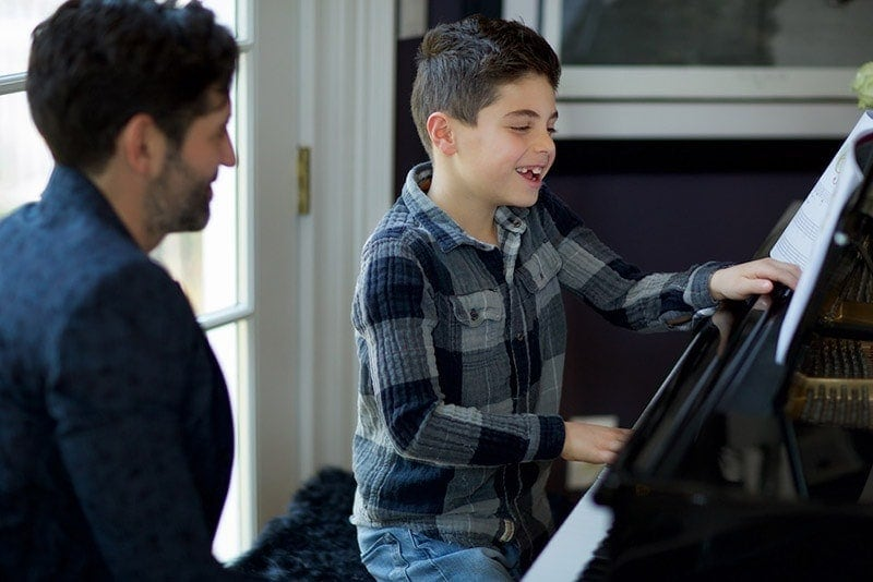 Boy learning piano with in home lesson