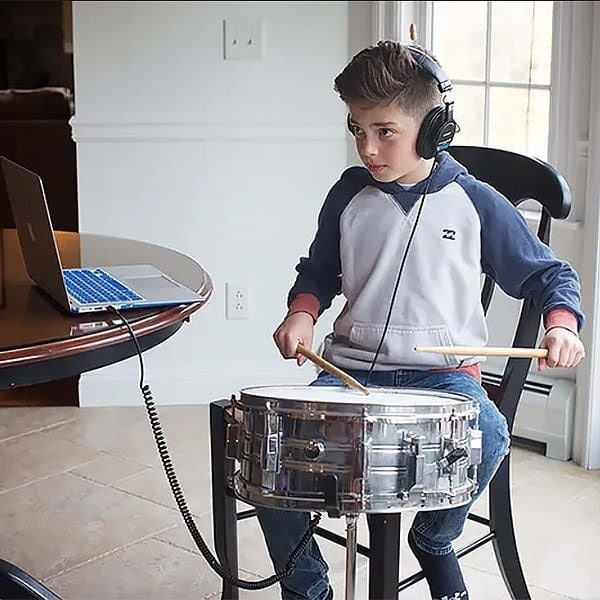 Online Drum Lessons- Boy learning drums with his laptop
