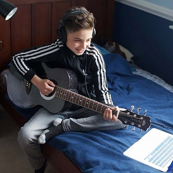 Learn Guitar Online Lesson - boy playing guitar with his laptop